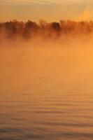 Mist rises from the Saint Lawrence River at sunrise on a cold winter morning, Iroquois, Ontario, Canada.