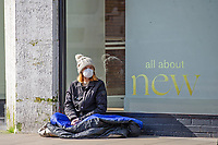 Pictured: A masked lady sat in Swansea City Centre during the Covid-19 Coronavirus pandemic in Wales, UK, Swansea, Wales, UK. Monday 23 March 2020