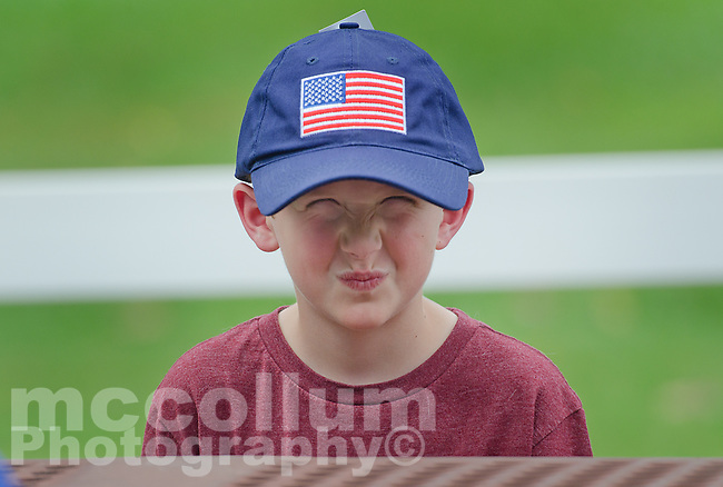 """Michael McCollum<br /> 8/2/18<br /> Alex Overman,7, at the reveal ceremony where it was announced to 13 year old Ryan Overman of west Knoxville that The Wish Connection is granting Ryan's wish to go to Washington DC and visit the White House at Carl Cowan Park, 10058 S Northshore Dr, Knoxville, TN, Thursday, August 2, 2018 at 5:45pm. Approximately 50-60 people attended, including the Overman family, friends, and AT&T Employees. The Bearden High School Cadets also attended and lead the pledge of allegiance.<br /> The AT&T Wish Connection is going to send Ryan, his family, and his service dog to Washington DC and while they are gone, the group of volunteers will be doing a makeover on his bedroom and turn it into the """"Oval Office"""" at the White House.<br /> Ryan was born two weeks prematurely on May 13, 2005. During the pregnancy he was classified as high risk due to a measured lack of growth and, after a brief stay in the hospital, he came home weighing only 4 lbs 5 oz. His development was much slower compared to his peers, such as not learning to walk until he was well over a year old, and he was much smaller. The Overman family worked with Tennessee Early Intervention Services (TEIS) when Ryan was about one year old and with their help they were able to get Ryan enrolled through TEIS to receive Occupational, Physical, and Speech Therapy. When Ryan turned three he transitioned from TEIS to the Knox County Early Intervention Program and began attending a special school to continue his therapies until he was old enough to enroll at Cedar Bluff Elementary and now is at Cedar Bluff Middle School. In 2016, Ryan was diagnosed to have retinitis pigmentosa, a degenerative disease of the retinas that under the best of circumstances causes severe tunnel vision, but more commonly results in complete blindness.<br /> Despite the physical difficulties that Ryan has had to endure over the last thirteen years, he continually brightens the lives of those around him. If someone is hu"""