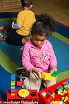 Education preschool 3-4 year olds girl making construction from plastic building bricks (Duplo)