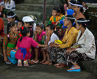 Bali, Indonesia.  Little Girls Talking While Waiting for a Dance Performance to Begin.  Pura Dalem Temple, Dlod Blungbang Village.