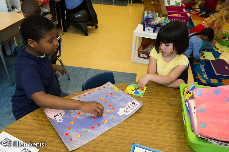 MR / Schenectady, NY. Zoller Elementary School (urban public school). Kindergarten inclusion classroom. Students play teacher-made board game at math learning center time. The game requires them to count and read numberals. Left: boy, 5, biracial; Right: girl, 5 MR: Was3, Coh2. ID: AM-gKw. © Ellen B. Senisi.