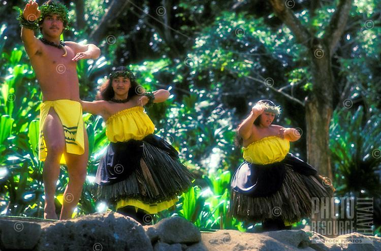A male and two female hula dancers perform a kahiko hula in a lush green setting at Waimea Falls Park.