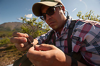 150620-JRE-7981E-0342 Joshua Quong a teacher and quail hunting guide from Mississippi, ties on a dry fly before fishing a remote interior Alaska stream for Arctic Grayling.