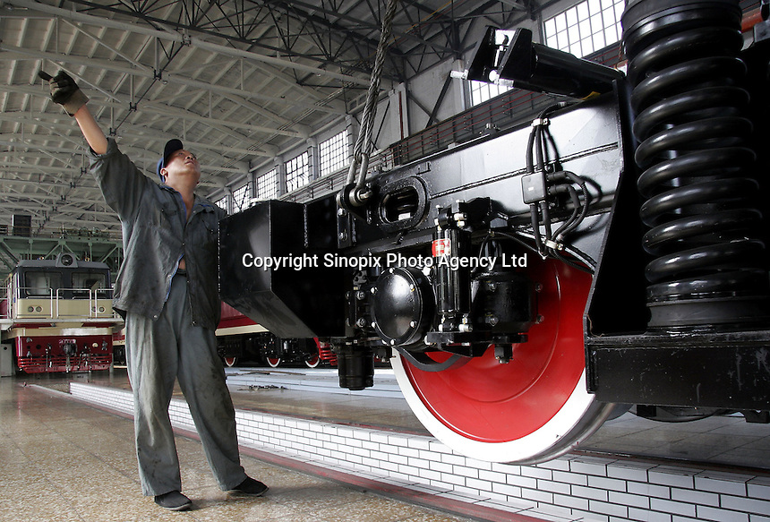 A Chinese worker directs the lowering of a locomotive's chassis at the state-owned Datong Electric Locomotive Co. LTD in Datong, Shanxi Province, China. China's developing economy has created a huge demand for faster and more powerful locomotive engines to move its people and goods within its vast and expanding railway network, the Datong company is currently working together with several western partners including Alstom of France and ABC of the U.S..05 Jul 2005
