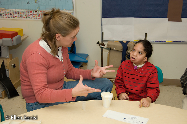 MR / Albany, NY.Langan School at Center for Disability Services .Ungraded private school which serves individuals with multiple disabilities.Teacher and child discuss outcome of science lesson. Lesson objectives are for students to predict whether a wrapped egg will break when dropped, as well as their use grasping and coordination skills. Students have mixed disabilities including cerebral palsy and muscular dystrophy.(other images from this sequence available) Boy: 7, African-American, Pierre Robin syndrome, limited verbal output with expressive and receptive language delays, has Passy Muir valve to redirect air flow to produce speech .MR: Ris4; Smi24.© Ellen B. Senisi