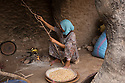 Morocco - Tidzi - Amina Hammoush, 40, breaks some wood to prepare the fire in order to roast the argan nuts before grinding them.