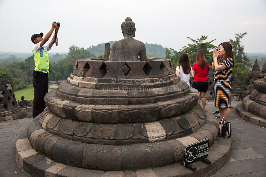 Borobudur, Java, Indonesia.  Security Guard Taking Visitors' Picture with their Point-and-Shoot Camera.
