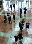 Office workers hustle through the lobby while others chat.