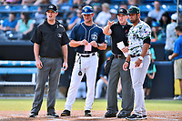 First base umpire Matthew Brown, Asheville Tourists manager Warren Schaeffer (13), home plate umpire Mark Stewart and Augusta GreenJackets manager Carlos Valderrama (21) exchange lineups and ground rules before a game between the GreenJackets and the Tourists at McCormick Field on July 15, 2017 in Asheville, North Carolina. The Tourists defeated the GreenJackets 2-1. (Tony Farlow/Four Seam Images)