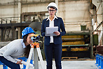 KJX4AJ Pensive building surveyor making notes about measurements while working with female engineer looking through optical theodolite in factory