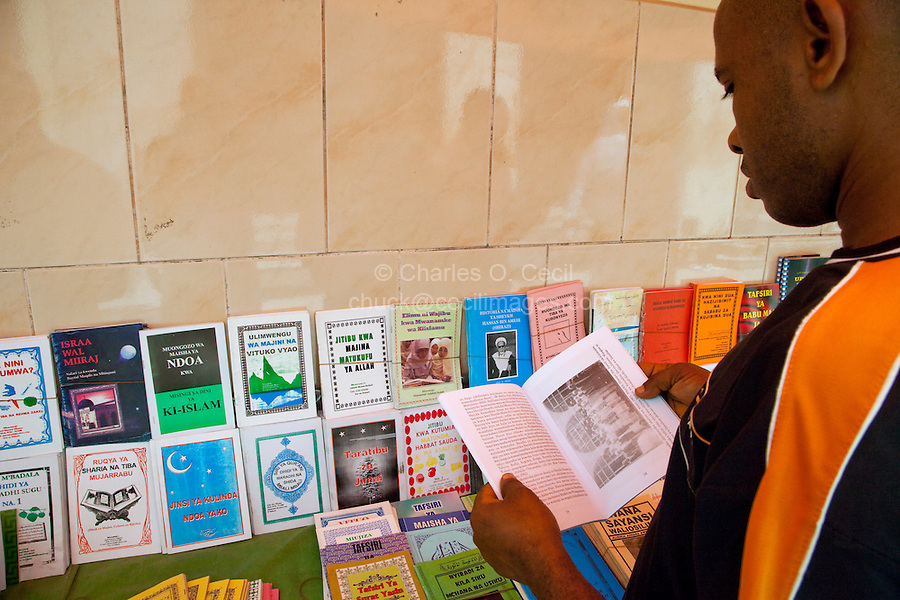 Zanzibar, Tanzania.  Potential Customer Examines a Book in a Bookstand selling books about Islam in Swahili or Arabic,  opposite the Jibril mosque in Stone Town.