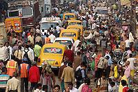 Ambassador taxis pass through crowds in central Kolkata, India. November, 2013