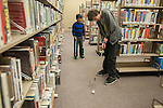 Ryan Fitzsimmons attempts a putt while being watched by fellow golfer Sohan Vadlakunta during the Mini Golf Night at the Carson City Library on Friday May 9, 2014. Kids and parents built a custom mini golf course throughout the library using anything at their disposal and engineering ideas to make a difficult course. Everything from tables to shelves were used to create creative courses.<br /> (Photo by Kevin Clifford/Nevada Photo Source)