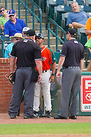 Greensboro Grasshoppers manager Jorge Hernandez (center) lets home plate umpire Kevin Morgan (left) know he did not like the final strike call during the South Atlantic League game against the Augusta GreenJackets at NewBridge Bank Park on August 11, 2013 in Greensboro, North Carolina.  The GreenJackets defeated the Grasshoppers 6-5 in game one of a double-header.  (Brian Westerholt/Four Seam Images)
