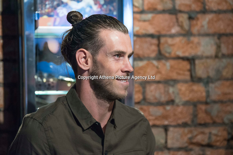 """Pictured: Gareth Bale at his Elevens Bar in Cardiff, Wales, UK. Thursday 12 July 2018<br /> Re: Last night (Thurday 12 July) Elevens Bar & Grill and the Football Association of Wales jointly hosted a Q&A evening with Gareth Bale. At the event, Gareth unveiled a new piece of memorabilia for Elevens – his match worn boots from this year's Champions League Final with which he scored that incredible overhead kick.<br /> The event, hosted at Elevens Bar & Grill was open to members of the public with doors opening at 6pm on Thursday evening. People started queueing from 3pm, with a cross-section of fans of all ages in Wales shirts and bucket hats. <br /> The Q&A, conducted by Ian Gwyn Hughes from the FAW, discussed all aspects of his career so far, from growing up in Cardiff to winning 4 Champions League medals with Real Madrid. On growing up in Whitchurch, Gareth said: """"My family were a huge influence on me growing up. My parents were so supportive, taking me here there and everywhere so I could play football. Growing up I can hardly remember not being with a football – I even took one to bed!""""<br /> There were a lot of youngsters in the audience, eager to hear from their hero. Gareth's advice to them? """"Work hard for what you want and who knows where that could take you.""""<br /> As a left-footer, Ryan Giggs,  Wales' national team manager was someone he looked up to growing up. Gareth mentioned it was great to beat Ian Rush's goal scoring record for Wales with his childhood idol as manager. """"I knew I'd levelled his record at half time, I needed one more to break it. The manager wanted to take me off but I said give me another 15 minutes to see if I can do it. Luckily on 61 minutes our goalkeeping coach took too long to do the substitution on the paper, so it gave me an extra minute. It worked out perfectly."""""""