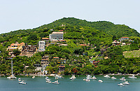 Inns, restaurants and homes perch on the hillside overlooking Zihuatanejo Bay in Zihuatanejo, Mexico. The gentle water in the bay, protected from waves by the mountains, makes the bay a popular place for swimming, sailing, parasailing, fishing, and kayaking.  (taken August 2007). Photo by Patrick Schneider Photo.com