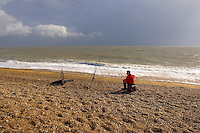 boy fishing off the shingle beach at Aldeborough, Suffolk, England