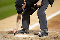 Home plate umpire Travis Godec cleans off the plate during the International League game between the Toledo Mud Hens and the Charlotte Knights at BB&T BallPark on April 23, 2019 in Charlotte, North Carolina. The Knights defeated the Mud Hens 11-9 in 10 innings. (Brian Westerholt/Four Seam Images)