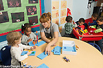 Education Preschool 2-3 year olds classroom scene female teacher working with small group of girls at table with peg and counting boards activity, group of boys playing at sand table nearby