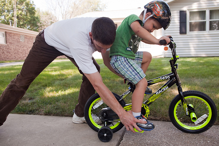 My husband helps our younger son ride his first bike.