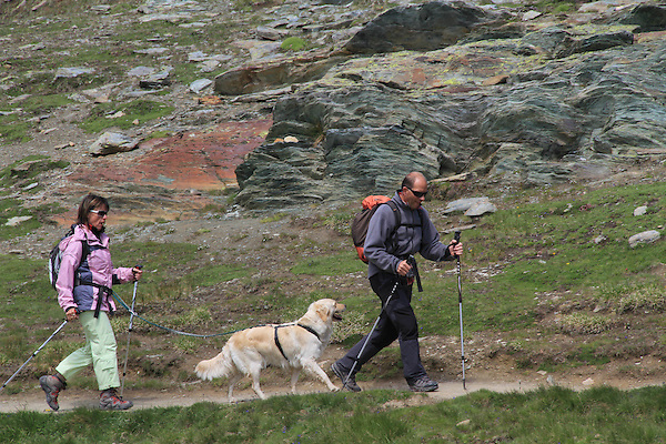 Couple hiking with their dog near the Matterhorn, above Zermatt, Switzerland. .  John offers private photo tours in Denver, Boulder and throughout Colorado. Year-round.