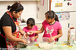 Family cooking at home mother and daughters ages 6 and 9 making tortillas