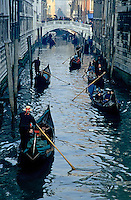 Tourists travelling on gondolas through a narrow canal, Venice, Italy.