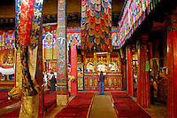 Buddhist pilgrims and tourists pay respects in the main hall of Ramoche Temple, with silk embroidered adorned columns, built in the 7th century, sister to the Jokhang Temple, Lhasa, Tibet, China.