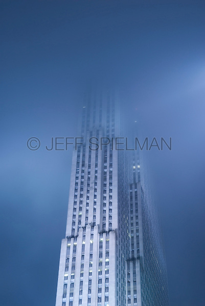 AVAILABLE FROM JEFF AS A FINE ART PRINT<br /> <br /> AVAILABLE FROM JEFF FOR LICENSING<br /> <br /> Upward View of 30 Rockefeller Plaza (also known as the GE Building/previously known as the RCA Building) on a Foggy Night, Rockefeller Center, Midtown Manhattan, New York City, New York State, USA