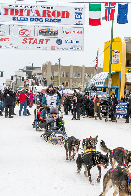 Zoya DeNure and team leave the ceremonial start line with an Iditarider and handler at 4th Avenue and D street in downtown Anchorage, Alaska on Saturday March 7th during the 2020 Iditarod race. Photo copyright by Cathy Hart Photography.com