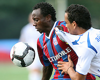 Mathew Mbuta #14 of Crystal Palace Baltimore grabs onto Hicham Aaboubou #2 of the Montreal Impact during an NASL match at Paul Angelo Russo Stadium in Towson, Maryland on August 21 2010. Montreal won 5-0.