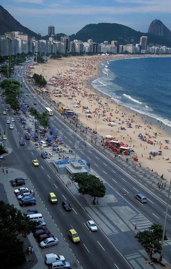 Copacabana Beach and Avenida Atlantica, with Sugar Loaf in background in late afternoon, Rio de Janeiro, Brazi