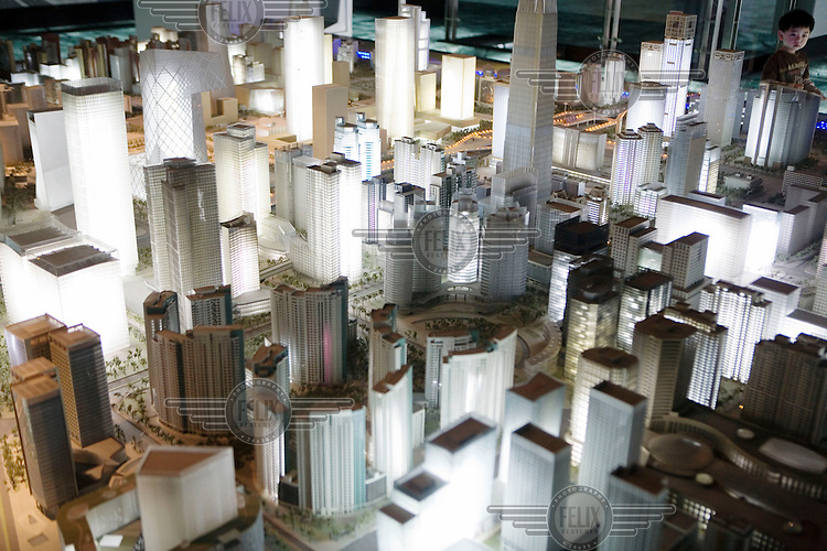 A child looks at an architectural model of the new plans for the central business district (CBD) area in Beijing at the Beijing Planning Exhibition Hall.