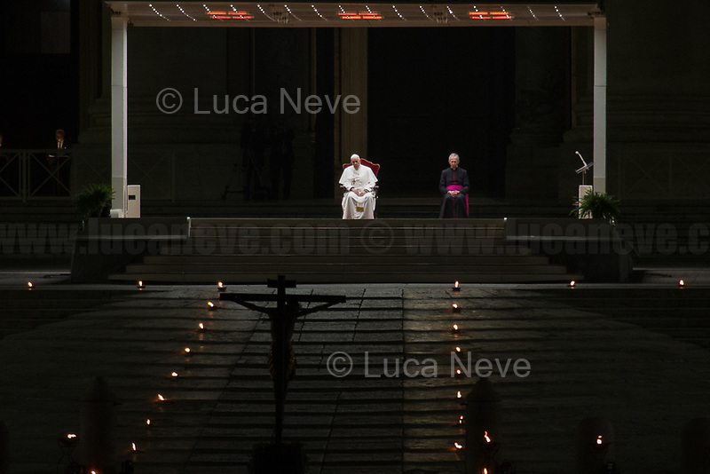 """Rome, 10/04/2020. On the evening of the Good Friday, Papa Francesco (Pope Francis, Jorge Mario Bergoglio) celebrated the Via Crucis (Way to the Cross: the final moments of the Passion, death and burial of Jesus Christ) in a spectral Saint Peter's Square where the path of the Cross was marked with burning torches located around the obelisk. These year, the traditional Via Crucis could not be held at the Colosseum, people were not allowed to attend it, and member of the press were kept really far from the event due to the spread of the Coronavirus (SARS-CoV-2 - infection: COVID-19) which already killed more than 100,000 people globally.      <br /> «[…] For 2020, the meditations for the fourteen """"Stations"""" along the Way of the Cross were prepared by the chaplaincy of the Due Palazzi House of Detention in the northern Italian city of Padua. Five prisoners, the family of a murder victim, the daughter of a man given a life sentence, the mother of another prisoner, a guard, and a priest who was convicted of a crime but eventually exonerated, were among those contributing their reflections on the Passion of the Lord, and how it bears on their own situations. […] With the path marked out by burning torches on the ground, the black Cross was carried around the obelisk at the centre of the Square, before coming to the door of the Basilica. The Cross was escorted by members of the Due Palazzi chaplaincy, and by members of the Health and Hygiene Directorate of the Vatican City State. […]» (1.).<br /> <br /> Footnotes & Links:<br /> 1. https://www.vaticannews.va/en/pope/news/2020-04/pope-francis-leads-good-friday-via-crucis-at-st-peter-basilica.html<br /> Video of the event (Source, Vaticannews.va) https://youtu.be/nxUTl7yBt7E"""