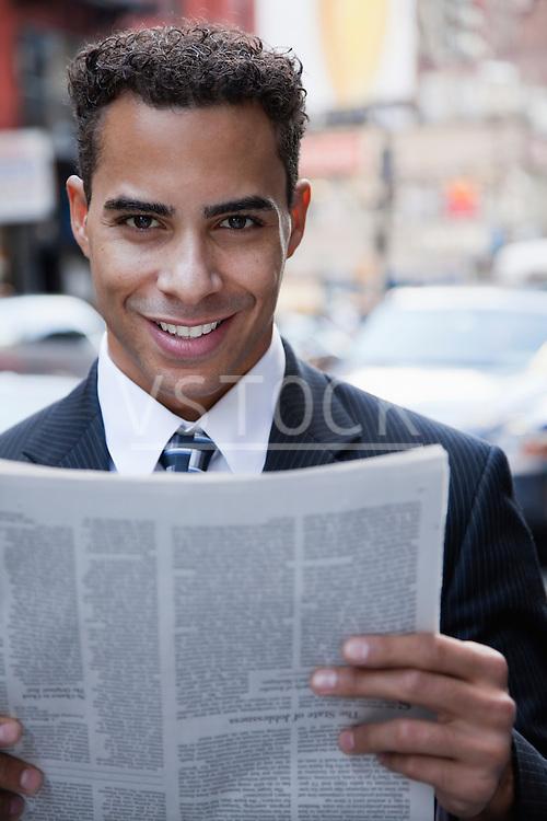 USA, New York, New York City, portrait of smiling businessman holding newspaper on street