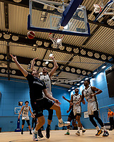 Evan Walshe of Surrey Scorchers shoes a basket under pressure from Evan MaxwellEvan of Newcastle Eagles during the BBL Championship match between Surrey Scorchers and Newcastle Eagles at Surrey Sports Park, Guildford, England on 20 March 2021. Photo by Liam McAvoy.