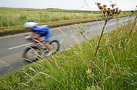 27 JUL 2013 - CROMER, GBR - A competitor makes his way along the coast road past the salt marshes at Salthouse, North Norfolk, Great Britain during The Anglian Triathlon (PHOTO COPYRIGHT © 2013 NIGEL FARROW, ALL RIGHTS RESERVED)