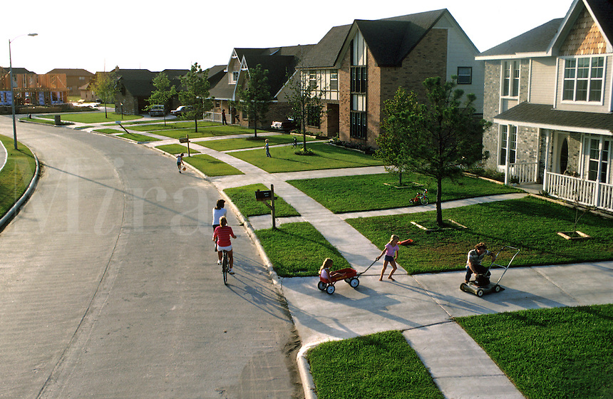 Adults riding bike, child sweeping driveway, 2 female children playing with little red wagon, 2 female adults talking in front of house, in new neighborhood, during late afternoon. Adults and Children. Houston Texas.