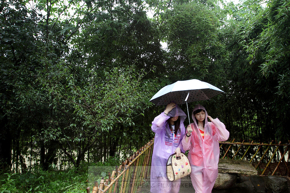 Tourists get caught in a rain shower in the Xixi wetlands which lie in the west of the city of Hangzhou. This is China's 'first national wetland park,' dubbed as such to act as a role model to all other wetlands in China and to supposedly show how to effectively manage and restore wetlands, notably urban wetlands. Zhejiang Province. China. 2010