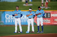 Omaha Storm Chasers outfielders Ryan McBroom (9), Kyle Isbel (3), and Edward Olivares (14) during the National Anthem before a game against the Iowa Cubs on August 14, 2021 at Werner Park in Omaha, Nebraska. (Zachary Lucy/Four Seam Images)