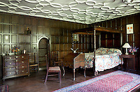 A 16th/17th century panelled bedroom complete with a small  four-poster bed and plasterwork decoration on the ceiling