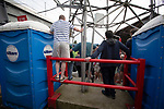 Home supporters standing between two Portaloos on the Ealing Road terrace as Brentford hosted Leeds United in an EFL Championship match at Griffin Park. Formed in 1889, Brentford have played their home games at Griffin Park since 1904, but are moving to a new purpose-built stadium nearby. The home team won this match by 2-0 watched by a crowd of 11,580.