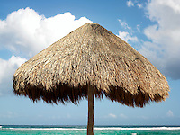 Mexico Quintana Roo Yucatan Peninsula Akumal Mayan Riviera,palapa against a cloudy blue sky and the sea