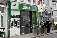 """Pictured: Police outside the Lloyds Bank on the High Street of Gorseinon, Wales, UK. Tuesday 20 November 2018<br /> Re: Two men with machetes are being hunted by police after trying to rob a Lloyds Bank in Gorseinon, near Swansea.<br /> Armed officers, police dogs and helicopter responded to the armed robbery at 10:00am on Tuesday.<br /> According to witnesses reports, the robbers """"came through the ceiling"""" and held a member of staff by the throat.<br /> South Wales Police said nobody was hurt during the incident.<br /> A witness said: """"They had a girl from Lloyds by the throat. After robbing the bank they used a car to drive off."""""""