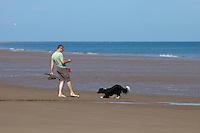 Holkham, Norfolk, England, 03/08/2009..Man walking a border collie dog on Holkham beach.