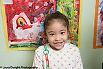 Education Preschool 4 year olds portrait of girl wearing jewelry made out of linking colored plastic chains, artwork on wall behind her