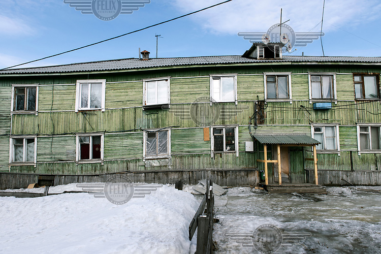 Snow covers the ground outside a decrepit two storey wooden apartment building that houses families despite its poor condition and lack of facilities.