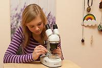 Kind, Mädchen mit Binokular, Stereolupe, Lupe, betrachtet eine Krabbe