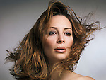 Beauty portrait of a woman with flying light brown hair and natural makeup in her early thirties isolated on gray background Image © MaximImages, License at https://www.maximimages.com